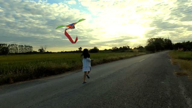 A cute little girl runs toward the camera with a kite.Sunset