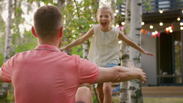 Niedliche kleine Mädchen rennt Vater, er steht auf einem Knie und umarmt sie. Glückliche Momente mit der Familie an einem sonnigen Sommertag im Garten spielen. – Video