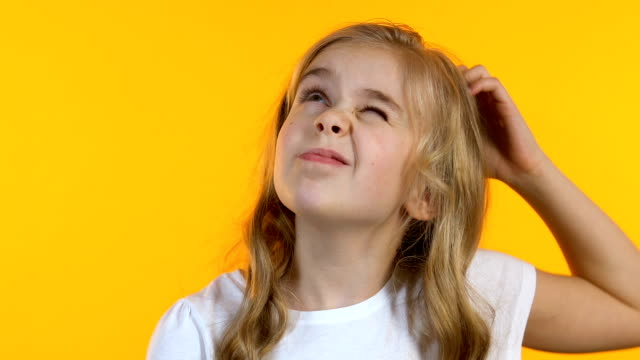 Cute little girl scratching head, trying to remember info, isolated background