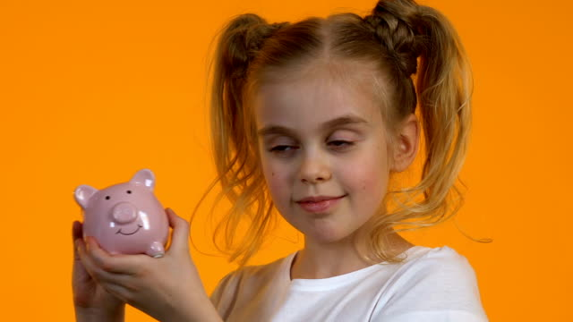 Cute little girl shacking piggy bank with coins and smiling, personal savings