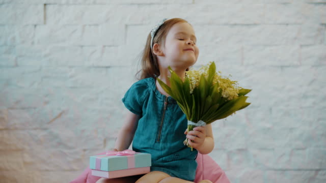 cute little girl shows flowers and a gift video
