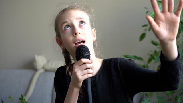 söt liten flicka sjunga karaoke hemma. - sångare artist bildbanksvideor och videomaterial från bakom kulisserna