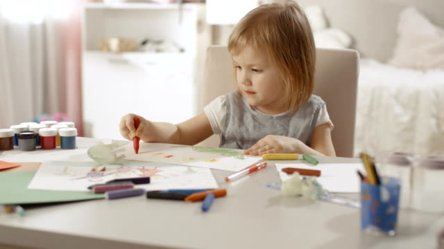 cute little girl sits at her table and draws with crayons. happy with the results she smiles.her room is pink, pretty drawings hanging on the walls, many toys lying around. - matita colorata video stock e b–roll