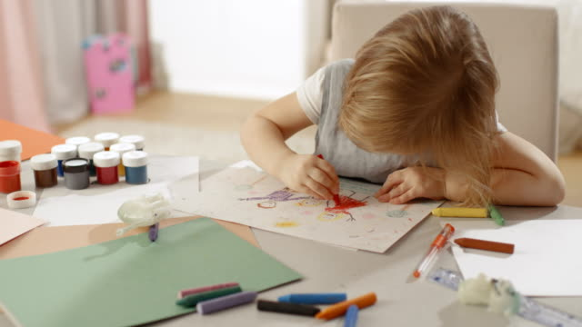 cute little girl sits at her table and draws with crayons. her room is pink and cosy. - matita colorata video stock e b–roll