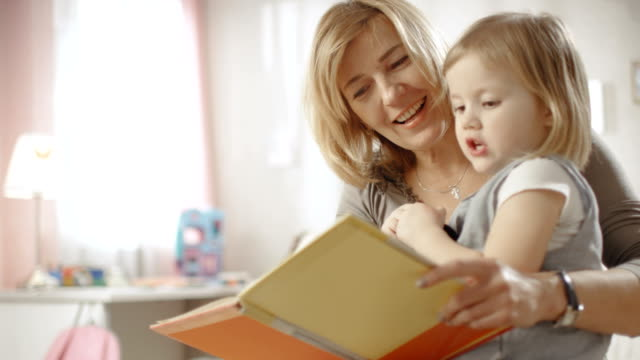 Cute Little Girl Sits on Her Grandmother's Lap and They Read Children's Book. Slow Motion. ビデオ