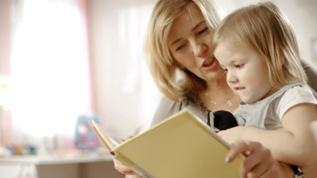 Cute Little Girl Sits on Her Grandmother's Lap and They Read Children's Book. Slow Motion. video