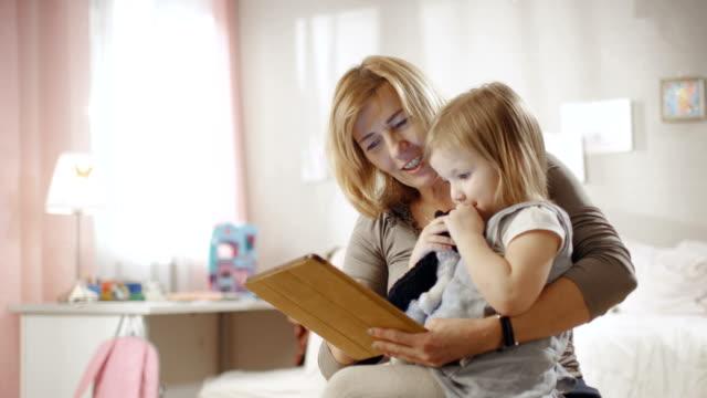 söt liten flicka sitter på hennes farmors lap och de använder tablet pc. slow motion. - digital reading child bildbanksvideor och videomaterial från bakom kulisserna