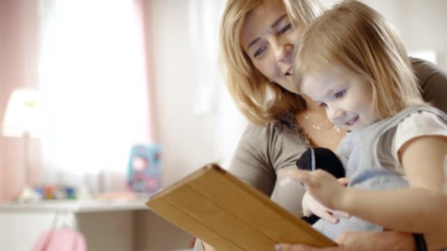 söt liten flicka sitter på hennes farmors lap och de använder tablet pc. - digital reading child bildbanksvideor och videomaterial från bakom kulisserna