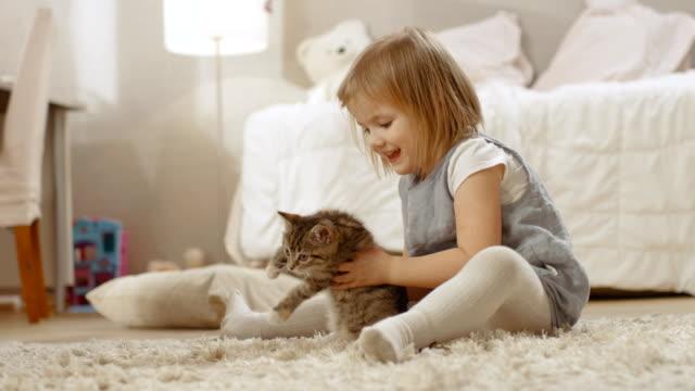 かわいい女の子が床に座って、幸せに彼女の好きな縞模様の子猫を保持しています。スローモーション。 - 子猫点の映像素材/bロール