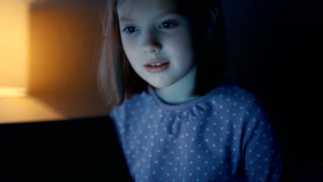 cute little girl sits with tablet computer on her bed at night. - sztuka i rzemiosło wytworzony przedmiot filmów i materiałów b-roll