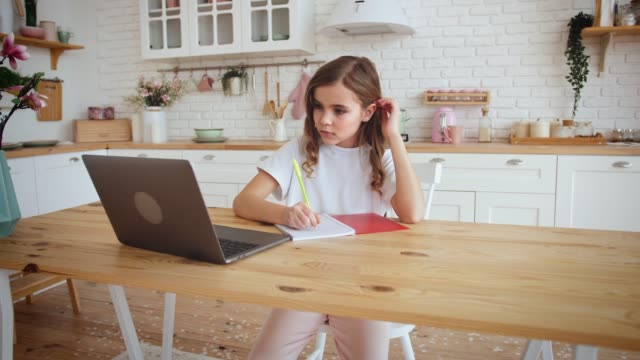 cute little girl sitting at kitchen table using laptop for distance learning, slow motion - solo una bambina femmina video stock e b–roll