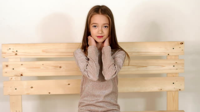 Cute little girl sitting on a bench in fashion Studio and posing for the camera