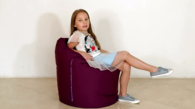 Phenomenal Cute Little Girl Sitting On Purple Bean Bag Sofa For Living Bralicious Painted Fabric Chair Ideas Braliciousco