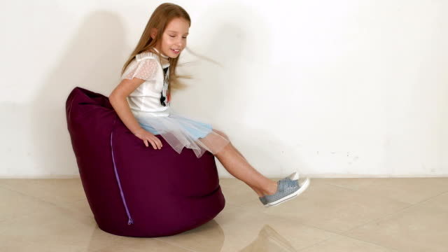Magnificent Cute Little Girl Sitting On Purple Bean Bag Sofa For Living Andrewgaddart Wooden Chair Designs For Living Room Andrewgaddartcom