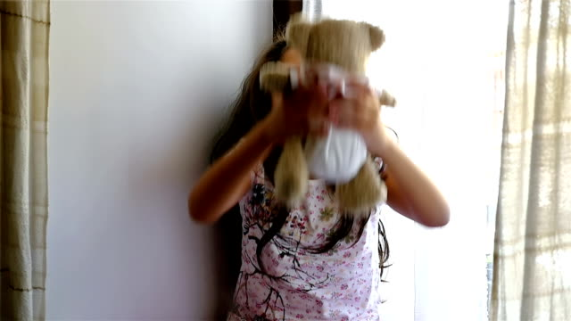 Cute little girl sitting on the windowsill, playing with bear toy, slow motion video
