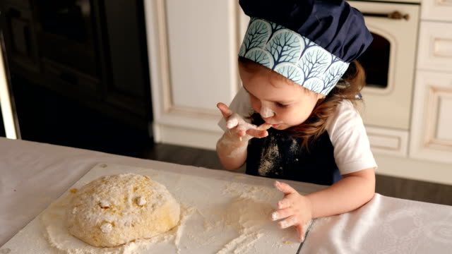 cute little girl smeared with flour licks her fingers with dough in the kitchen. - leccare video stock e b–roll