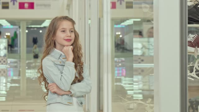 Cute little girl smiling to the camera, examining fashion store display