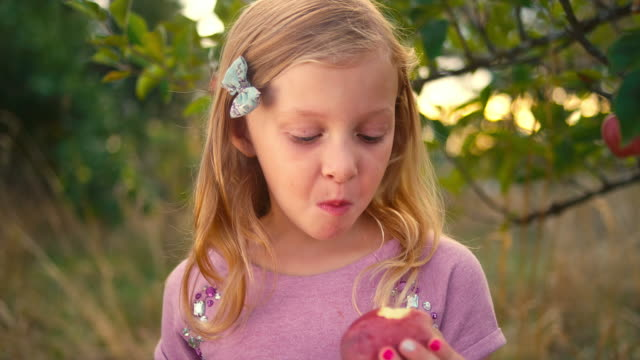 A cute little girl takes a bite out of a fresh apple from a tree and makes a face, and then smiles video
