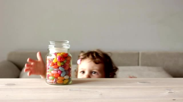 cute little girl takes jar of colorful candy - dolci video stock e b–roll