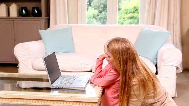 vídeos de stock e filmes b-roll de pequena menina usando laptop com a mãe - coffee table