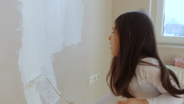 Cute little girl using paint roller and painting wall in white color