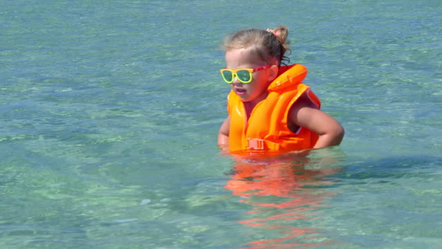 vídeos de stock, filmes e b-roll de linda garotinha usando colete salva-vidas na água turquesa sobre férias na praia - inflável