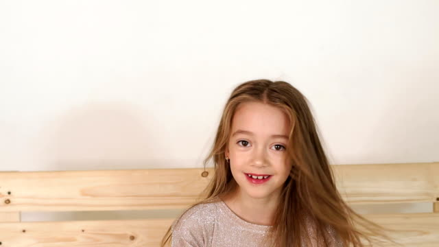 Cute little girl with long hair posing in Studio sitting on wooden bench.