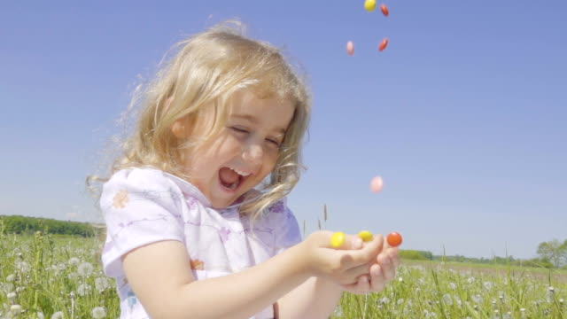 cute little girl with pleasure catches multicolored candy falling from above. joyful cheerful child laughing outdoors. summer sunny day. slow motion. - ловить стоковые видео и кадры b-roll