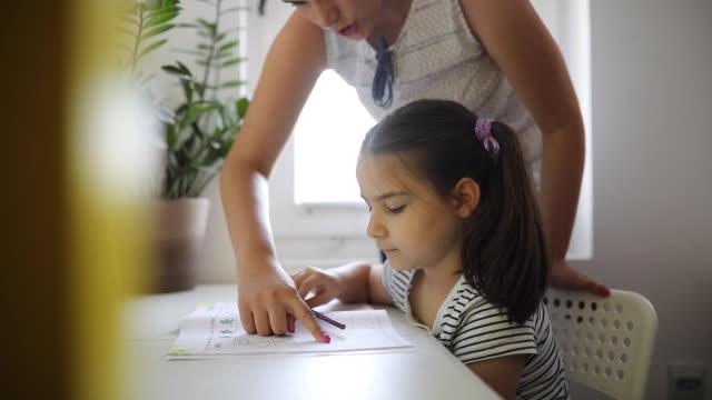 sevimli küçük kız yazma ve öğretmen yardımı ile öğrenme - çalışma kitabı stok videoları ve detay görüntü çekimi