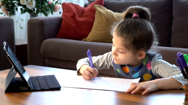 cute little girl writing on white paper. e-learning from home - didattica a distanza video stock e b–roll