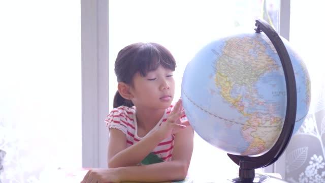 söta små flickor tittar på globen. - bordsjordglob bildbanksvideor och videomaterial från bakom kulisserna
