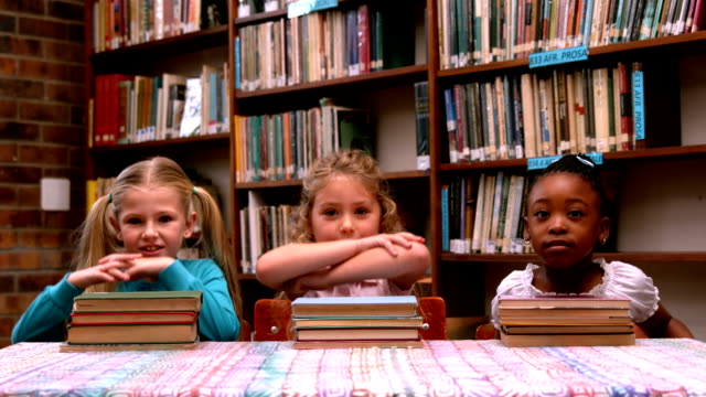 Cute little girls posing with library books video