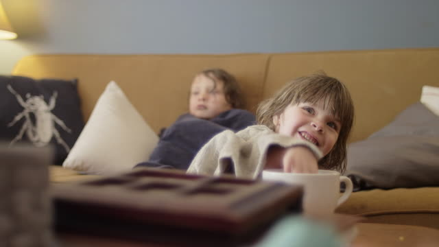 Cute little girls wrapped in towels watching TV and eating snacks Cute little girls wrapped in towels watching TV and eating snacks wearing a towel stock videos & royalty-free footage