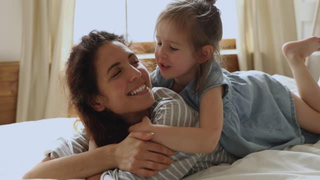 cute little kid daughter embrace kiss mom lying on bed - serdeczny filmów i materiałów b-roll
