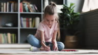 istock Cute little kid girl drawing colored pencils playing on floor 1210528844