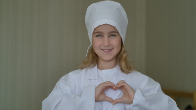 Cute Little Kid Girl Wear Medical Uniform makes heart sign with her hands. Portrait of Creative Child Smiling Wearing Doctor Uniform with Stethoscope Celebrating Doctor Day. Heart Symbol Love Thanks.
