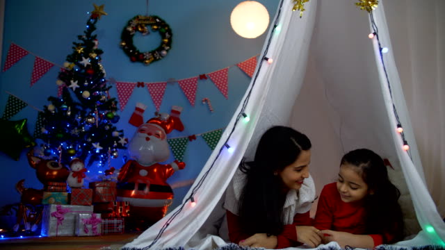 Cute little kid spending quality time with her mom while lying in the tent house - winter season Beautiful Indian mother and daughter enjoying a perfect fun day on Christmas with a colorful festive background indian family stock videos & royalty-free footage