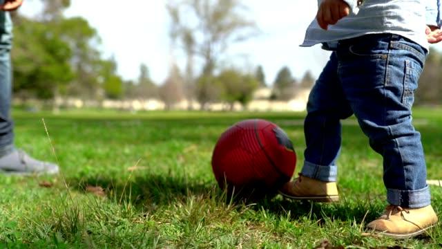 vídeos de stock e filmes b-roll de cute little mixed-race boy kikcing red ball on lawn - criança pequena