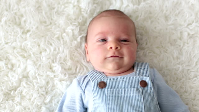 Cute little newborn baby, looking into the camera, happily smiling, lying down in bed video