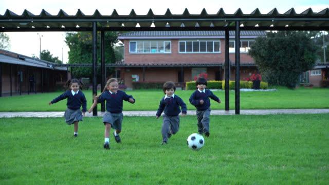 学校の遊び場でサッカーをして遊ぶかわいい小さな生徒 - 男の子点の映像素材/bロール