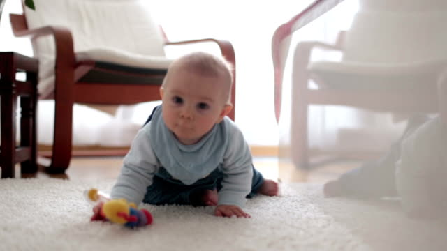 Cute little toddler baby boy, playing at home on the floor in bedroom, smiling happily Cute little toddler baby boy, playing at home on the floor in bedroom, smiling happily crawling stock videos & royalty-free footage