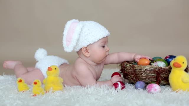かわいい小さな幼児男の子、カラフルなイースターエッグと小さな装飾的なアヒルで遊んで分離ショット、ベージュの背景 - イースター点の映像素材/bロール