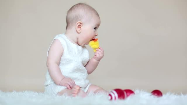 stockvideo's en b-roll-footage met schattige kleine peuter baby jongen, spelen met kleurrijke paaseieren en kleine decoratieve eenden, geïsoleerd shot, beige achtergrond - background baby