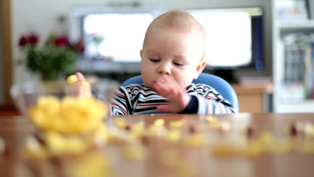 vídeos de stock e filmes b-roll de cute little toddler boy eating cornflakes and smiling in the kitchen. - boca suja