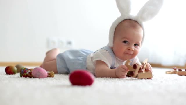 かわいい小さな幼児子供、男の子は、日当たりの良いリビング ルーム チョコレート イースターのウサギとカラフルなイースターエッグと遊ぶ ビデオ