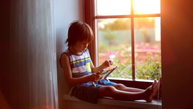 söt liten toddler barn, leker med abacus på ett fönster - abakus bildbanksvideor och videomaterial från bakom kulisserna