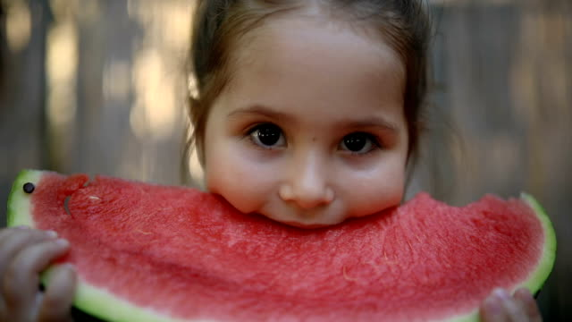 cute little toddler eating a slice of watermelon - succoso video stock e b–roll