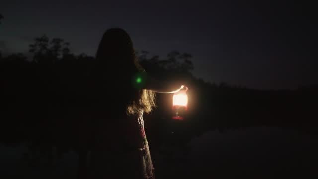 Cute long hair girl holding lantern at night in halloween Time