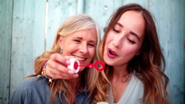 Cute mature mother and young daughter blowing bubbles together outdoors video
