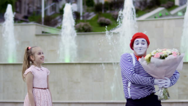 Cute mime in red beret give bouquet of flowers to a little girl Cute mime in red beret give bouquet of flowers to a little girl. Urban actor entertains people at the street. The mime gesticulate his facial expressions. greasepaint stock videos & royalty-free footage
